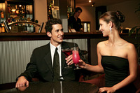 A couple in dinners wear having a toast in the bar