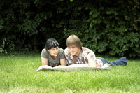 A couple lying on the grass analyzing a map