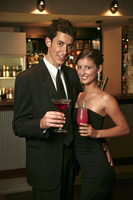 A couple posing with their drinks in the bar