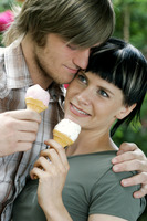 A couple standing near to each other holding ice-creams