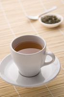 A cup of tea with tea leaves in the background