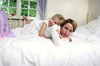 A girl lying on the bed hugging her mother from the back