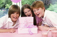 A girl posing with her brothers in front of her birthday presents