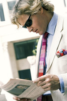 A guy in business suit and sunglass reading newspaper