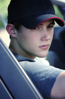 A guy with cap sitting in the car