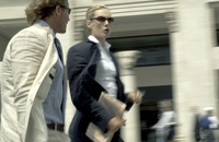 A man and woman in business suit walking in a very fast pace