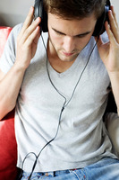 A man holding the headphone, listening to music