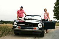 A married couple standing beside their roofless car