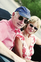 A married couple with sunglasses driving around in their roofless car