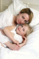 A short hair woman lying on the bed hugging her daughter