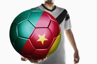 A soccer player holding cameroon soccer ball