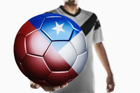 A soccer player holding chile soccer ball
