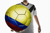A soccer player holding colombia soccer ball
