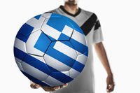 A soccer player holding greece soccer ball