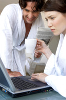 A woman in bathrobe using laptop while her husband watching
