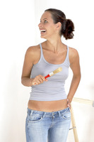 A woman in jeans smiling while holding a brush