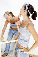 A woman measuring a wood while her friend is checking the paint on the wall