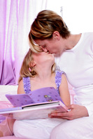 A woman sitting on the bed kissing her daughter