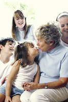 A young girl kissing her grandmother while the others watching