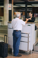 Airline check-in attendant returning businessman's passport at the airport check-in counter
