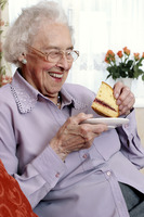 An old bespectacled woman sitting on the couch eating cake