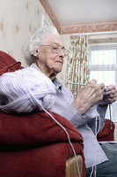 An old bespectacled woman sitting on the couch knitting