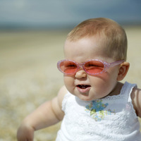 Baby girl with sunglasses sitting on the beach