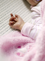Baby sleeping in the crib with the focus on her tiny hand