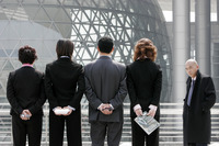Back shot of business man and women standing in a row hiding their stuff