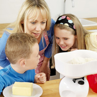 Boy and girl measuring flour on weight scale, woman watching