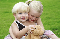 Boy and girl playing teddy bear in the park