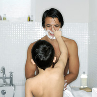 Boy applying shaving foam on his father's nose