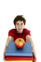 Boy carrying a stack of books with a red apple on top