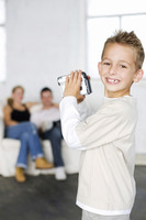 Boy filming parents with camcorder