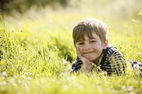 Boy lying forward on grassy field
