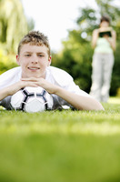 Boy lying forward on the grass with his chin resting on a soccer ball