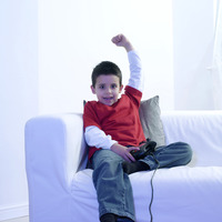 Boy raising his hand while playing with video game console