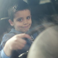Boy sitting in the car holding the steering wheel