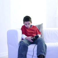 Boy sitting on the couch playing with video game console