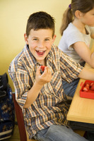 Boy smiling at the camera while holding a strawberry