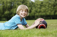Boy with soccer ball lying forward on the field
