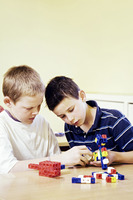Boys assembling plastic blocks
