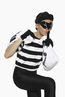Burglar with bags of money showing hushing sign