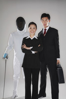 Business people and a man in fencing suit posing for the camera