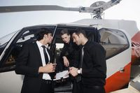 Business people discussing by the helicopter