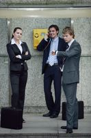 Business people waiting for businessman talking on public telephone