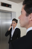 Business people waiting for elevator, businesswoman talking on the phone