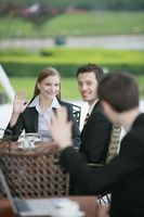Business people waving at each other at outdoor cafe