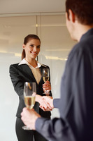Business people with champagne, shaking hands