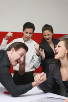Businessman and businesswoman arm wrestling on table, the others cheering